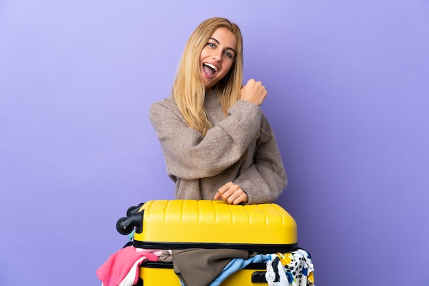 勝利を祝っている紫色の壁を越えて服の完全なスーツケースを持つ若いウルグアイブロンドの女性