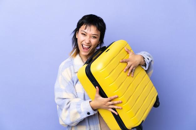 旅行スーツケースと休暇で休暇で孤立した紫以上のウルグアイの若い女性と驚いた