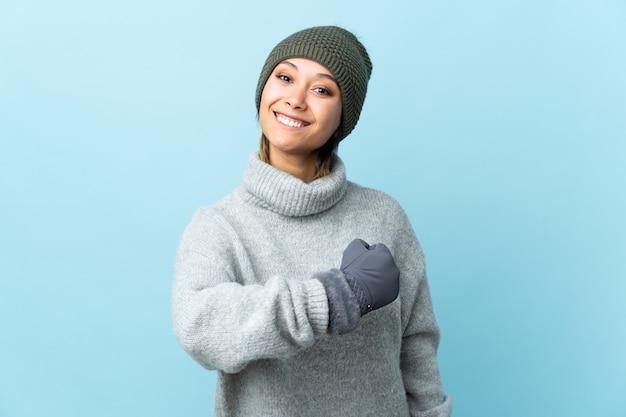勝利を祝う青に分離された冬の帽子を持つウルグアイ少女