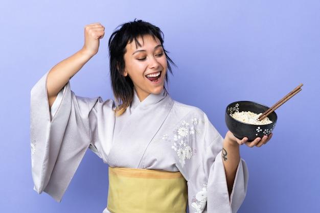 箸で麺のボウルを押しながら勝利を祝う孤立した青い服を着た若い女性