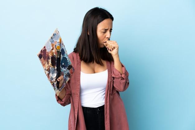 たくさんの分離された青い咳パレットを保持している若いアーティスト女性