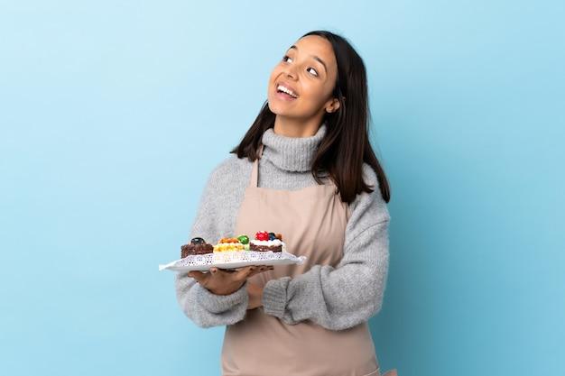 孤立した青い幸せと笑顔の上に大きなケーキを置くパティシエ