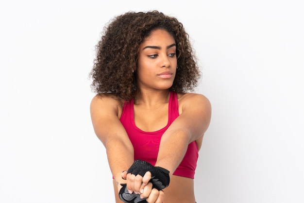 Молодая афро-американская женщина спорта изолированная на белой протягивая руке