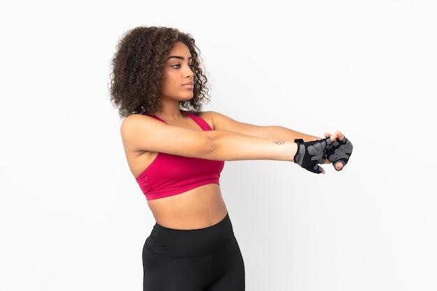 Молодая афро-американская женщина спорта изолированная на белый протягивать