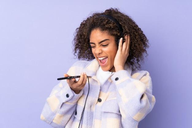 Молодая афро-американская женщина изолированная на фиолетовой слушая музыке с чернью и петь