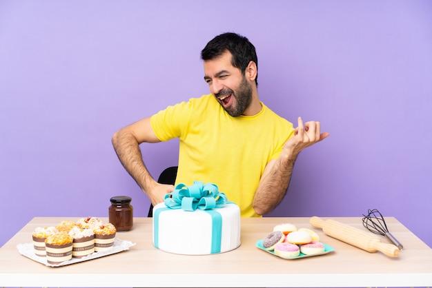 ギターのジェスチャーを作る大きなケーキを持つテーブルの男