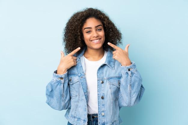 Молодая афро-американская женщина изолированная на сини давая жест больших пальцев руки вверх