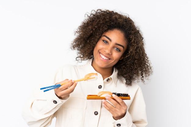 白で隔離される寿司を保持している若いアフリカ系アメリカ人女性
