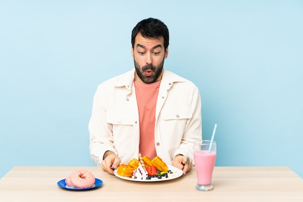 朝食のワッフルとミルクセーキを持つテーブルで男