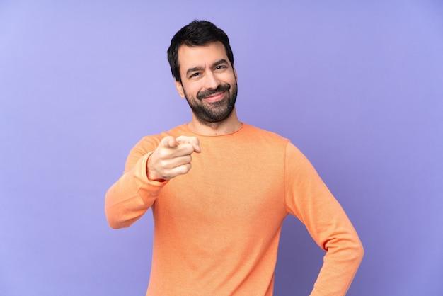 Кавказский красавец над изолированных фиолетовый указывает пальцем на вас с уверенным выражением