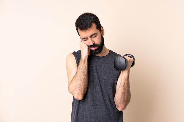 疲れて退屈な表情で孤立した上に重量挙げを作るひげを持つ白人スポーツ男