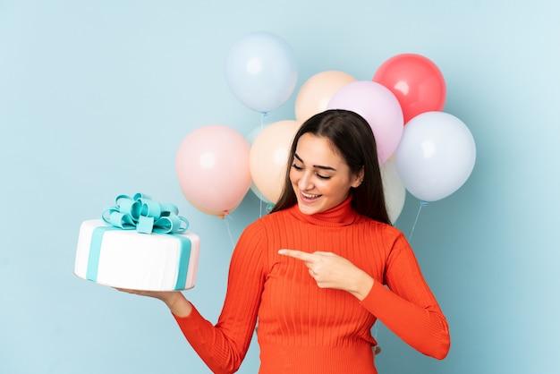 Молодая женщина с много воздушных шаров, изолированных на синем