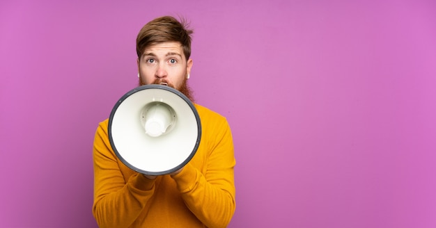 Рыжий мужчина с длинной бородой на изолированных фиолетовый кричал через мегафон