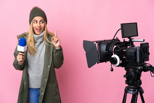 マイクを押しながら指を上に向けてアイデアを考えて孤立したピンクの上のニュースを報告するレポーター女性
