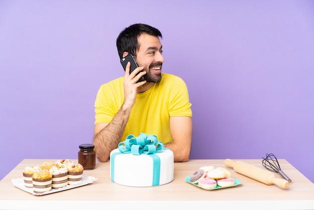Человек в столе с большим тортом
