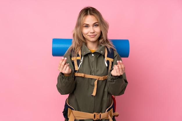 お金のジェスチャーを作るピンクの大きなバックパックを持つティーンエイジャー登山少女