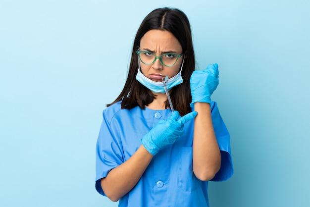若いブルネットの混血の歯科医の女性が分離されたツールを保持している遅れているジェスチャーを作る