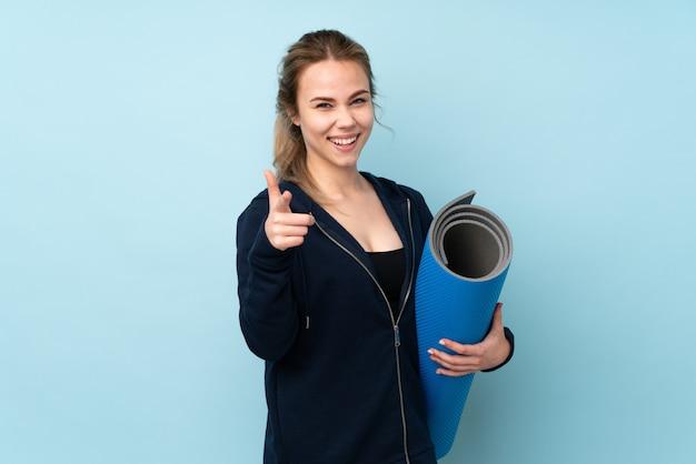 Девушка подростка держа циновку изолированный на сини указывая к фронту и усмехаться