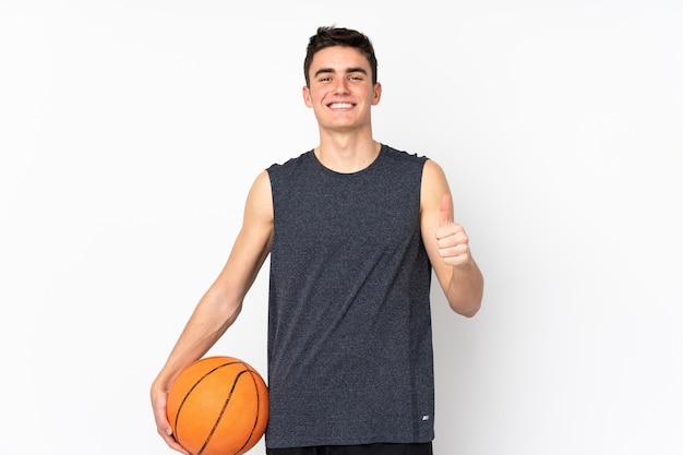 ハンサムな若いバスケットボール選手の男が孤立した壁を越えてバスケットボールを再生し、親指で
