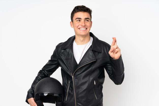 Мужчина держит мотоциклетный шлем на белом с скрестив пальцы
