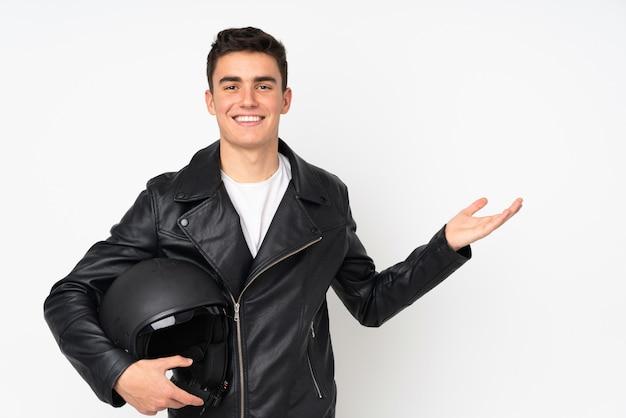 Мужчина держит мотоциклетный шлем, изолированные на белом, протягивая руки в сторону за приглашение прийти