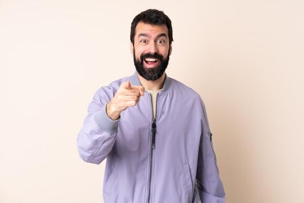 Кавказский человек с бородой носить пиджак над изолированной удивлен и указывая спереди