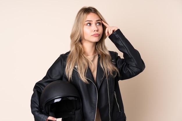Русская девушка с мотоциклетным шлемом, изолированная на бежевом, с сомнениями и размышлениями
