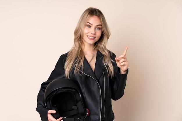 Русская девушка с мотоциклетным шлемом на бежевом фоне показывает палец вверх