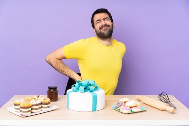 腰痛に苦しんでいる大きなケーキを持つテーブルの男