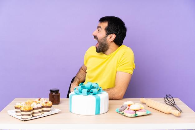 驚いた表情で大きなケーキを持つテーブルの男