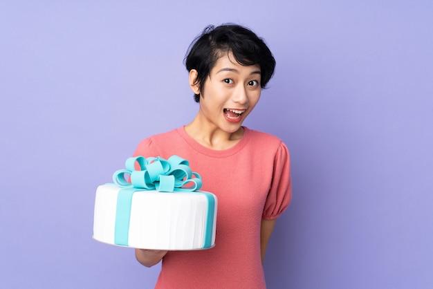 紫の壁に大きなケーキを持って短い髪の若いベトナム人女性