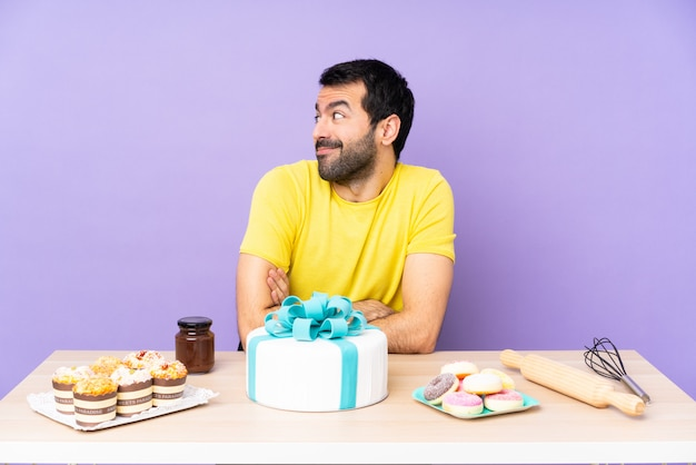 Человек в таблице с большой торт, глядя на одну сторону
