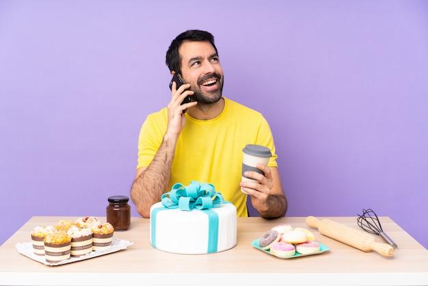 電話で話している大きなケーキを持つテーブルの男
