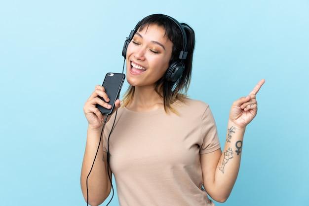 Молодая женщина над изолированным голубым космосом слушая музыка с чернью и петь
