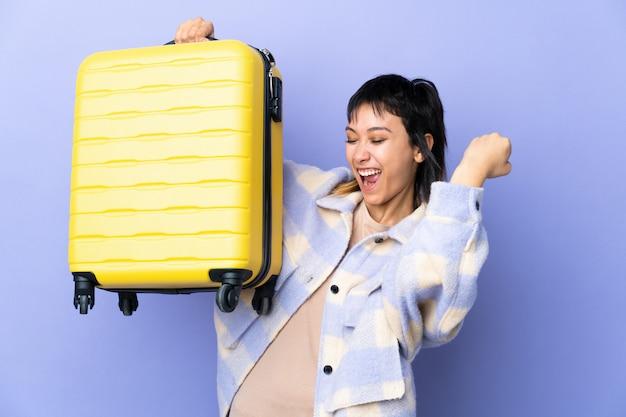 旅行スーツケースと一緒に休暇で孤立した紫色の空間上の若い女性