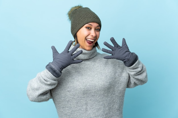 Молодая женщина в зимней шапке на синем фоне с удивленным выражением лица