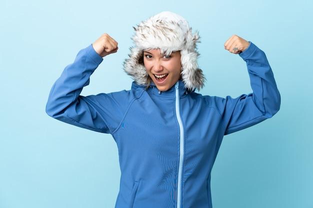 勝利を祝って青いスペースで分離された冬の帽子を持つ若い女性