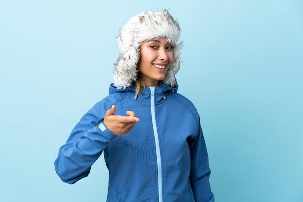 青い空間に分離された冬の帽子を持つ若い女性はあなたに指を指す