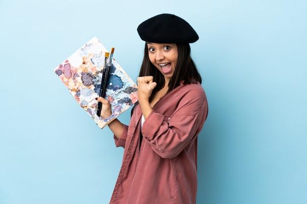 勝利を祝っている孤立した青い空間にパレットを置く若いアーティストの女性