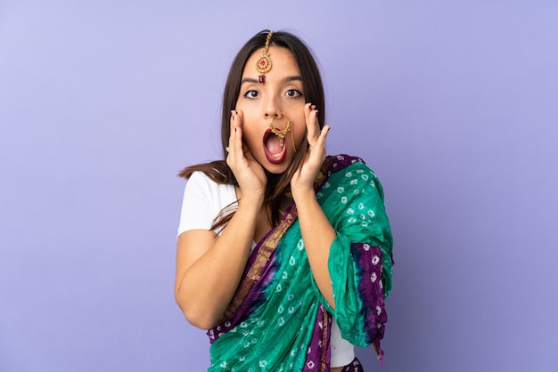 勝者の位置で勝利を祝っている紫色のスペースに分離された若いインド人女性