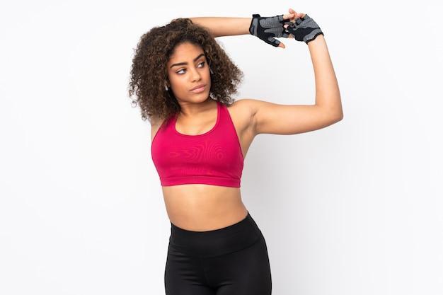 Молодая афро-американская женщина спорта изолированная на протягивать пустого пространства