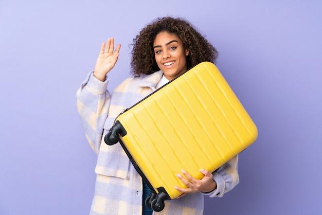 Молодая афро-американская женщина изолированная на фиолетовом космосе в каникулах с чемоданом перемещения и салютовать