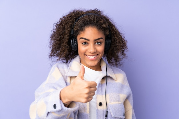 Молодая афро-американская женщина изолированная на фиолетовом космосе слушая музыка и с большим пальцем руки вверх