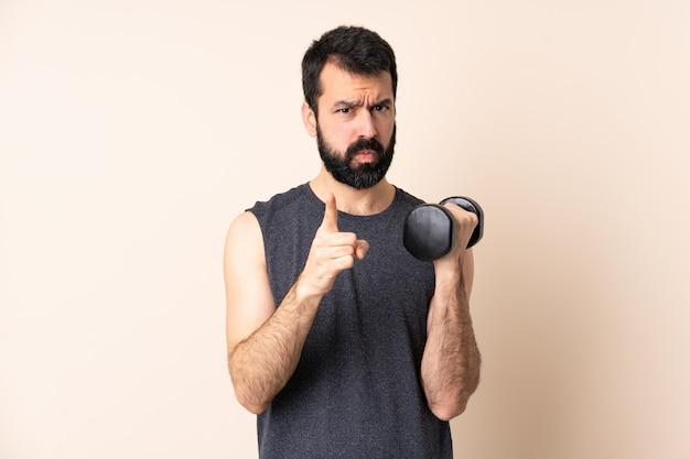 ひげと分離されたスペースに重量挙げを作る不満と正面を指している白人のスポーツ男