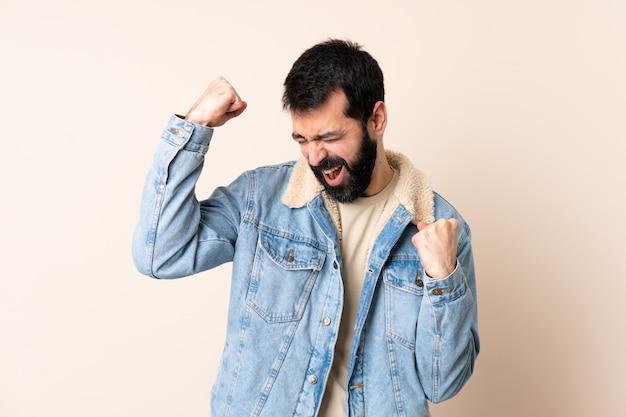 勝利を祝っている孤立したスペースの上のひげを持つ白人男