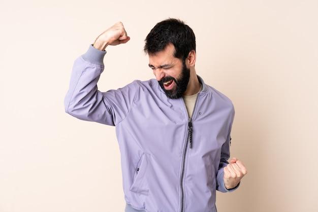 勝利を祝っている孤立したスペースの上にジャケットを着てひげを持つ白人男