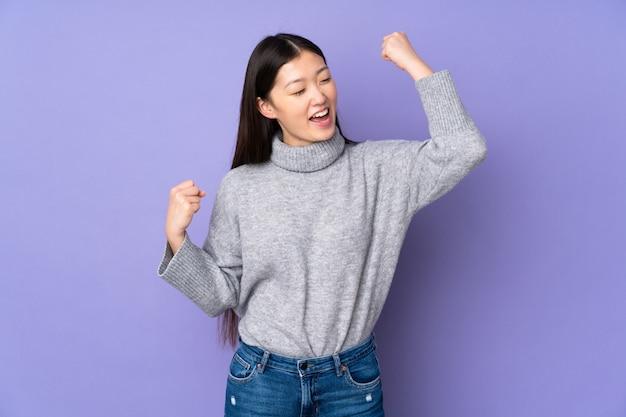 勝利を祝う孤立したスペースの上の若いアジア女性