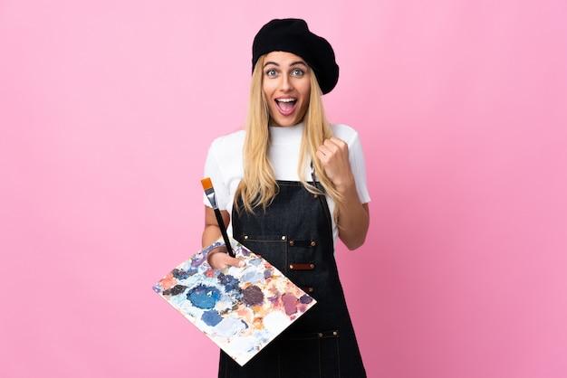 勝利を祝っている孤立したピンクのスペースにパレットを置く若いアーティストの女性