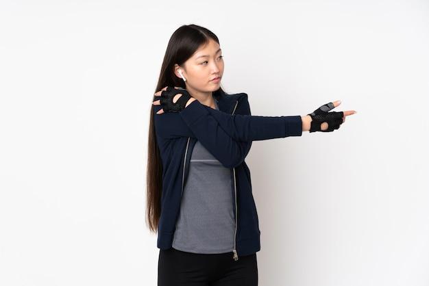 腕を伸ばすホワイトスペースに分離された若いスポーツアジア女性