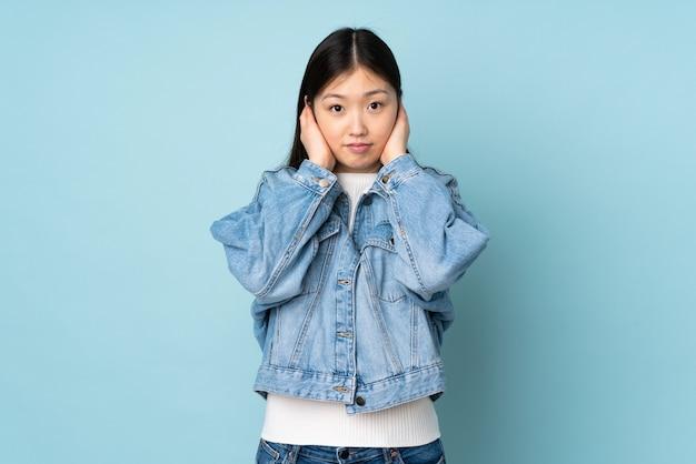 Молодая азиатская женщина изолированная на космосе расстроенная и покрывая уши